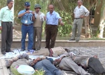 UN staff Amer Al-Kaissy, holding camera, is observing bodies of the PMOI / MEK members, massacred in Camp Ashraf, Iraq on 1 September 2013. He was the first outside observer who visited the camp on the day of the massacre and bravely reported the killings to the world.